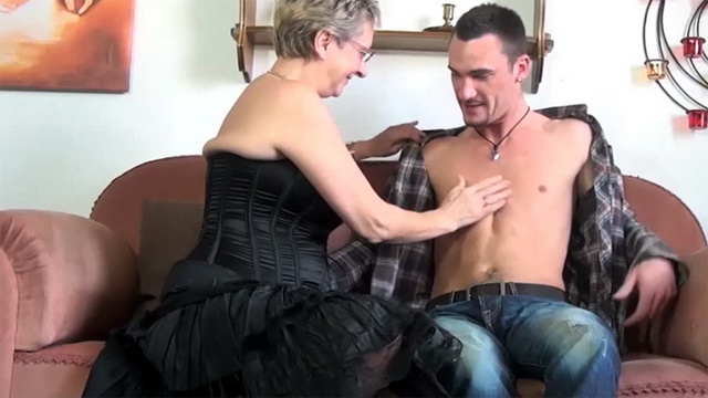 Buxom dolled-up mature strips to her black basque and stockings for a taste of young meat
