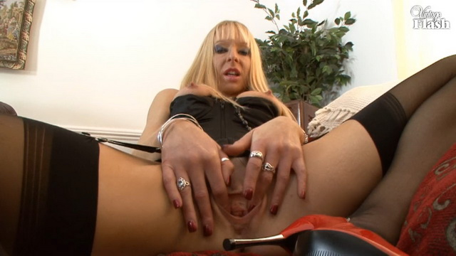 British blonde milf Michelle Manzer in black corset and stockings, red stiletto heels spreads her pussy lips