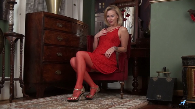 Seductive UK milf Lucy Lauren parades all her assets in a little red dress with matching stockings