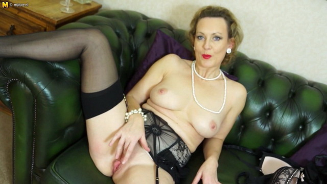 Smart British mature Betsy Blue strips showing the tops of her gartered stockings
