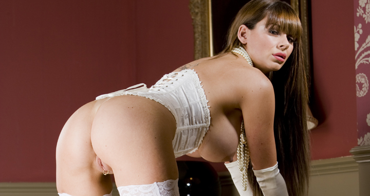 British glamour babe Ree Petra in a white corset and nylons riding a tied up stud