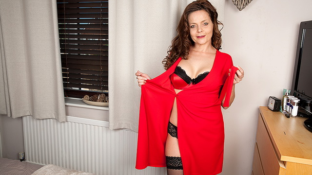 Sultry UK milf Gemma Gold wears red with matching bra and thong complete with black nylons and heels