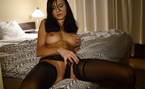 Busty babe in fine black holdups masturbating on the bed topless