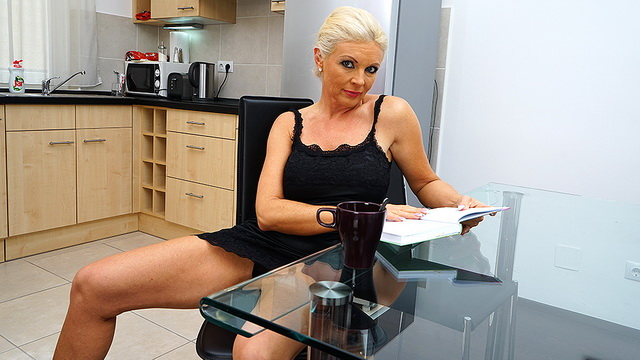 Blonde housewife rubs her thong-clad pussy in the kitchen while reading a book and drinking her tea