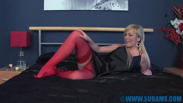 UK blonde Jessica Foxx in red stockings and black satin nightie pulls down her panties to finger her pussy on the bed