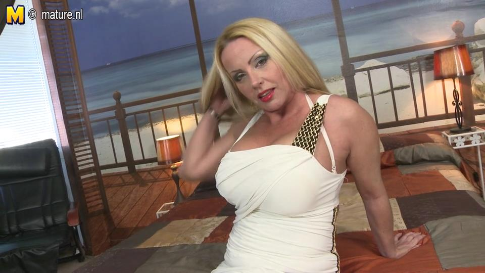 Blonde milf bombshell bares her huge globes and stuffs a dildo between her legs in white fishnets