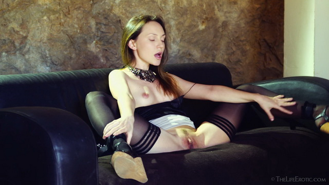 Upskirt teaser Nataly Von cuffs her legs in black stockings and wedges to a couch to rub her clit