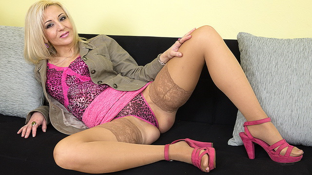Luscious blonde milf in pink strips to her tan holdups and opens up slim legs for wet fingering