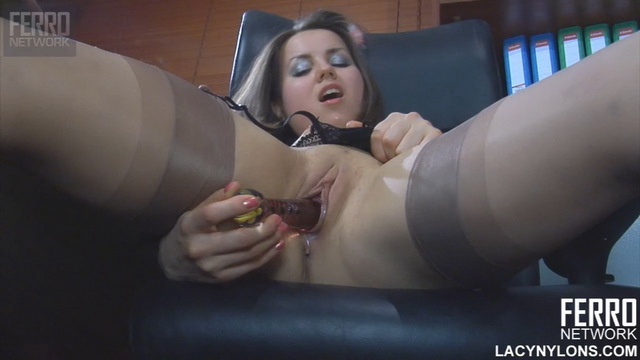 Doll-faced office babe Mishelle A. mounts her working table for stockinged dildo toying