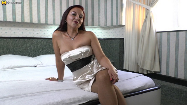 Latina mommy Bella in a strapless dress and gartered stockings pleasures herself