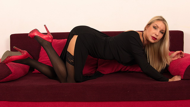 Blonde milf stunner Petra M opens long legs in black holdups and red pumps to play with her pink toy