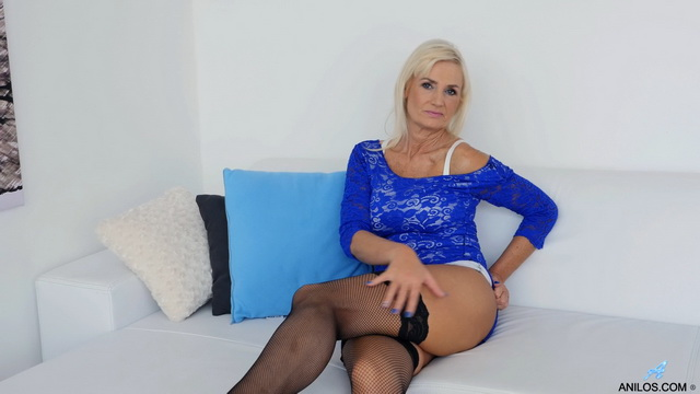 Busty Czech mature Roxana Hanova fondles her long legs in black fishnets before rubbing her clit