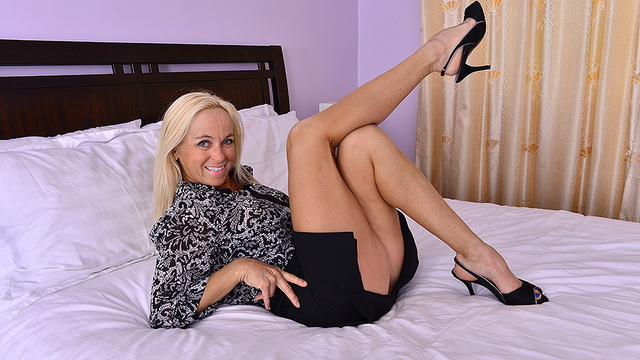 Blonde mommy Dani Dare fingers on a white bed stripping to her thong set & heels