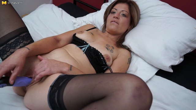 Horny British milf Emma Cee spreads her slim black-stockinged legs for her purple plastic lover
