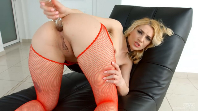 Blonde anal slut Luna Melba wiggles her ass in red fishnet suspender tights before using a glass toy