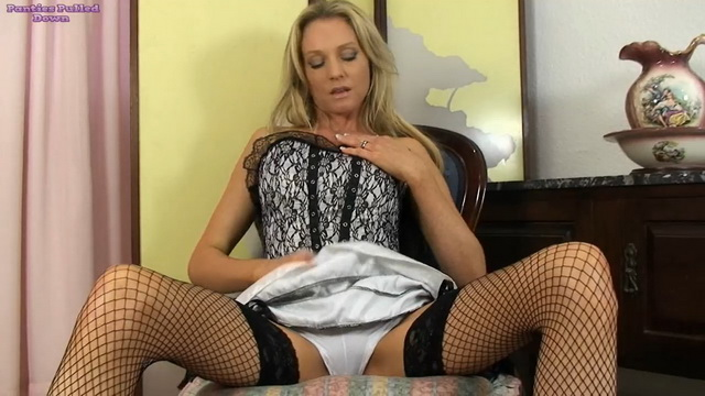 UK blonde Angel Price rides up her skirt exposing black fishnets & white panties