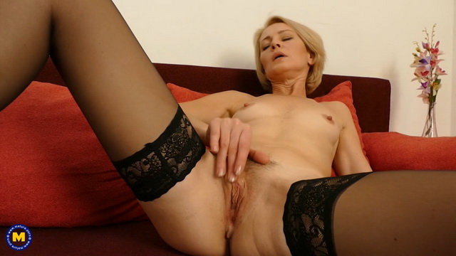 Slim-bodied mature Artemia dildo toying in her clingy dress, stockings and heels