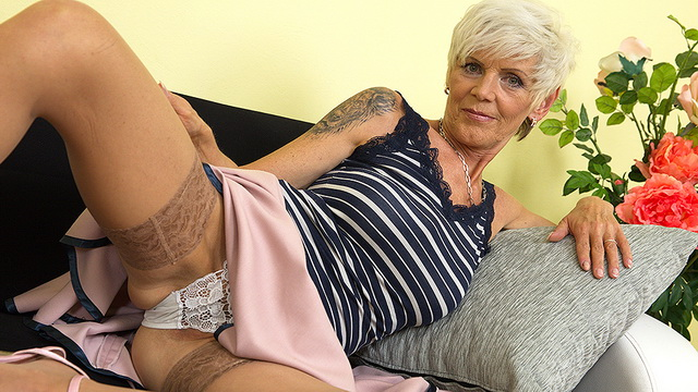 Slim yet busty mom rides up her skirt to show the tops of tan lacy holdups and finger her wet hole