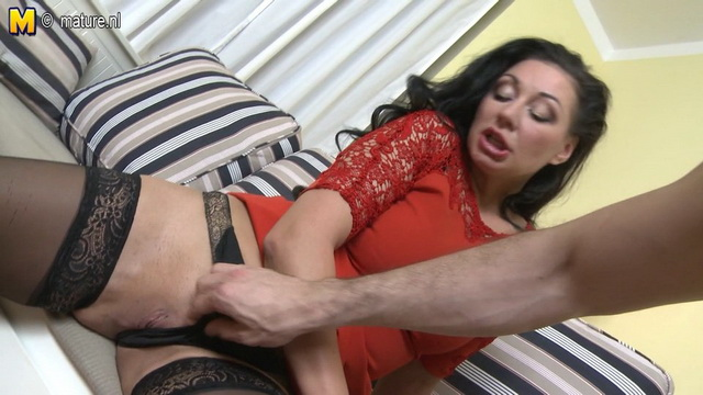Dressy brunette milf Eva Ann strips her red gown and opens legs in black holdups for a good bang